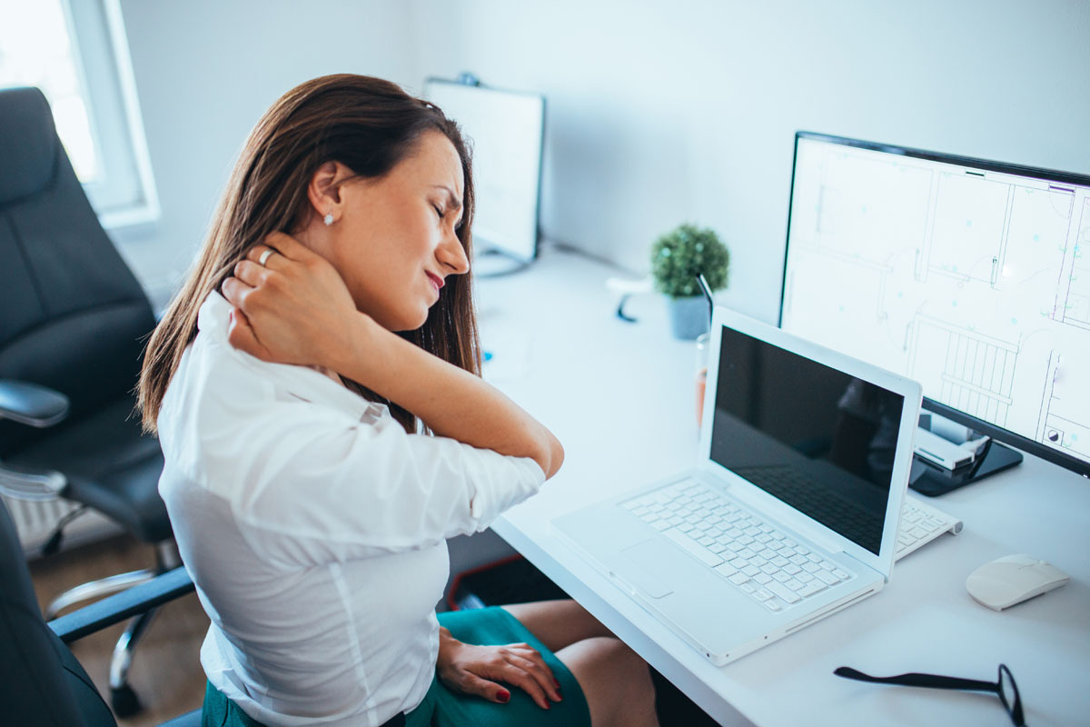 woman with neck pain at a computer